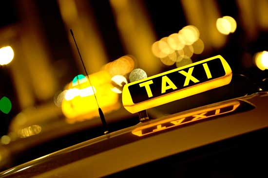 "A ""TAXI"" sign with its light on, indicating it is available"